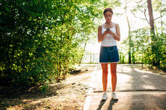 Mujer con el reproductor de audio que hace aptitud en parque de la ciudad Imagenes de archivo