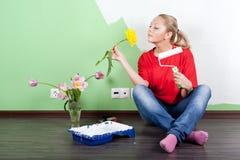 Mujer con el rodillo de la flor y de pintura en manos Fotografía de archivo