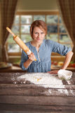 Mujer con el rodillo en la cocina, retrato emocional brillante foto de archivo