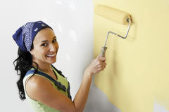 Mujer con el rodillo que aplica la pintura amarilla en una pared Imagen de archivo