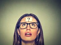 Mujer con el signo de interrogación Mujer pensativa que mira para arriba Fotografía de archivo