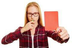 Mujer con el silbido que muestra una tarjeta roja Fotografía de archivo