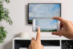 Mujer con el smartphone conectado con el aparato de TV fotografía de archivo