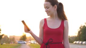Mujer con el smartphone que se opone en la calle al camino con la conducción de los coches almacen de metraje de vídeo