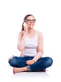 Mujer con el smartphone que se sienta en el piso, tiro del estudio, aislante Fotografía de archivo