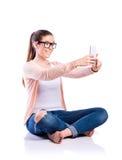 Mujer con el smartphone que se sienta en el piso, tiro del estudio, aislante Imagenes de archivo