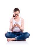 Mujer con el smartphone que se sienta en el piso, tiro del estudio, aislante Imágenes de archivo libres de regalías