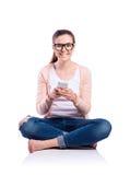 Mujer con el smartphone que se sienta en el piso, tiro del estudio, aislante Imagen de archivo libre de regalías