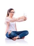 Mujer con el smartphone que se sienta en el piso, tiro del estudio, aislante Foto de archivo