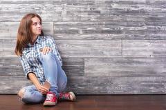 Mujer con el smartphone que se sienta en piso Imagen de archivo libre de regalías