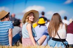 Mujer con el sombrero, adolescentes, festival del verano, sentándose en hierba Foto de archivo