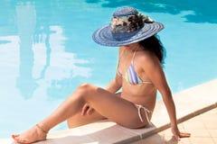 Mujer con el sombrero azul que broncea en la piscina Fotografía de archivo