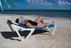 Mujer con el sombrero de paja grande que toma el sol en la playa Imagen de archivo libre de regalías