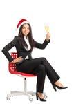 Mujer con el sombrero de Papá Noel que sostiene un vidrio de vino Imagen de archivo libre de regalías