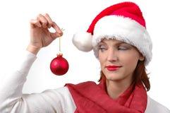 Mujer con el sombrero de Santa con el ornamento de la Navidad Imágenes de archivo libres de regalías