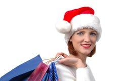 Mujer con el sombrero de Santa con los bolsos de compras Foto de archivo libre de regalías