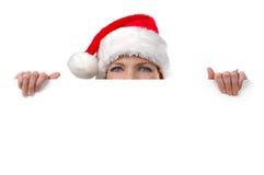 Mujer con el sombrero de Santa que lleva a cabo la muestra en blanco Imagenes de archivo