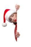 Mujer con el sombrero de Santa que lleva a cabo la muestra en blanco Foto de archivo