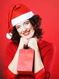 Mujer con el sombrero de Santa que sostiene el bolso de compras, Imagenes de archivo