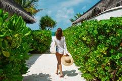 Mujer con el sombrero del bolso y del sol que va a varar Foto de archivo