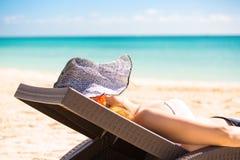 Mujer con el sombrero del sol que disfruta de la colocación que se sienta de la opinión del mar en una silla de playa Imágenes de archivo libres de regalías