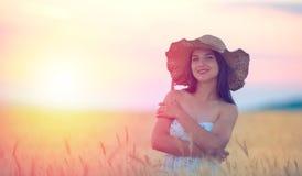 Mujer con el sombrero del verano en campo de trigo en la puesta del sol Fotografía de archivo