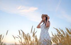 Mujer con el sombrero del verano en campo de trigo en la puesta del sol Fotos de archivo libres de regalías