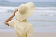 Mujer con el sombrero que mira el mar fotos de archivo