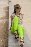 Mujer con el sombrero que se sienta en un banco cerca de la playa Fotografía de archivo libre de regalías
