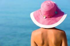 Mujer con el sombrero rosado que mira el mar Imagen de archivo