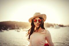 Mujer con el sombrero y las gafas de sol que presentan en la puesta del sol con el mar en el fondo foto de archivo