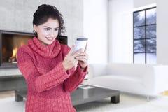 Mujer con el suéter y con el teléfono móvil en casa Fotos de archivo