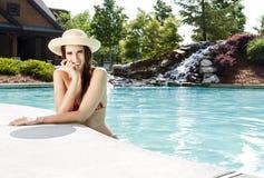 Mujer con el sunhat en la piscina Fotografía de archivo