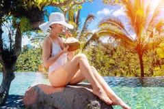 Mujer con el sunhat en la piscina que bebe un coco imagen de archivo libre de regalías