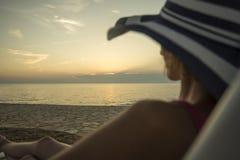 Mujer con el sunhat que pasa por alto el océano imágenes de archivo libres de regalías