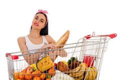 Mujer con el supermercado de la carretilla de las compras Imagen de archivo libre de regalías