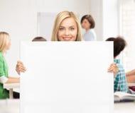 Mujer con el tablero en blanco blanco en la escuela Fotos de archivo