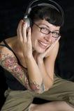 Mujer con el tatuaje y los auriculares Imagen de archivo libre de regalías