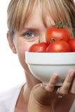 Mujer con el tazón de fuente de tomates Imagen de archivo libre de regalías