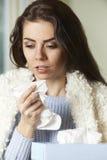 Mujer con el tejido que se sostiene frío y el estornudo Imágenes de archivo libres de regalías