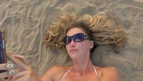 Mujer con el teléfono celular en la playa almacen de metraje de vídeo