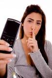 Mujer con el teléfono celular que da instrucciones para ser silencioso Imagen de archivo libre de regalías