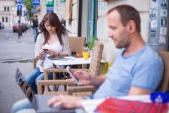 Mujer con el teléfono celular y el hombre con el ordenador portátil y el teléfono móvil que se sientan en un café. Imágenes de archivo libres de regalías