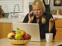 Mujer con el teléfono celular y la computadora portátil Foto de archivo libre de regalías