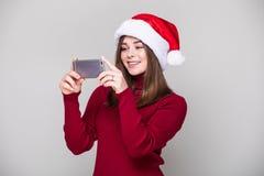 Mujer con el teléfono con el sombrero de santa Foto de archivo