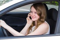 Mujer con el teléfono detrás de la rueda del coche Fotos de archivo libres de regalías