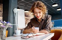Mujer con el teléfono en café Fotos de archivo libres de regalías