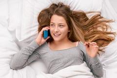 Mujer con el teléfono en cama Fotos de archivo libres de regalías
