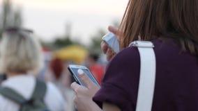 Mujer con el teléfono en el aire libre, communicat de la chica joven en redes sociales en el partido, femenino con el teléfono mó almacen de video