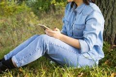 Mujer con el teléfono en la hierba Imagen de archivo libre de regalías